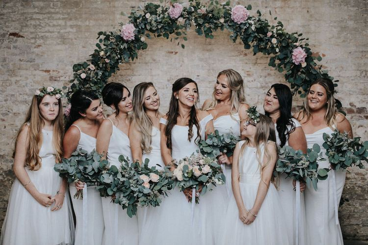 Bridal Party in White Standing in Front of a Floral Moon Gate