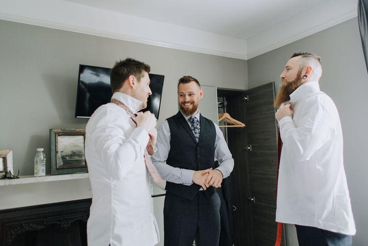 Groomsmen putting on wedding ties