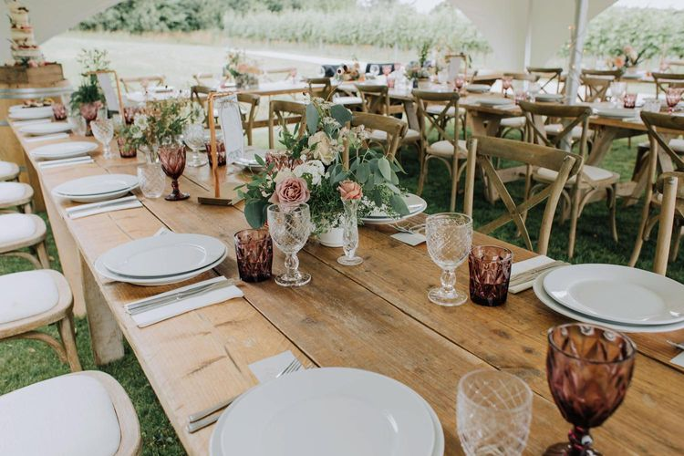 Wedding reception table decor with coloured goblets and flower centrepieces