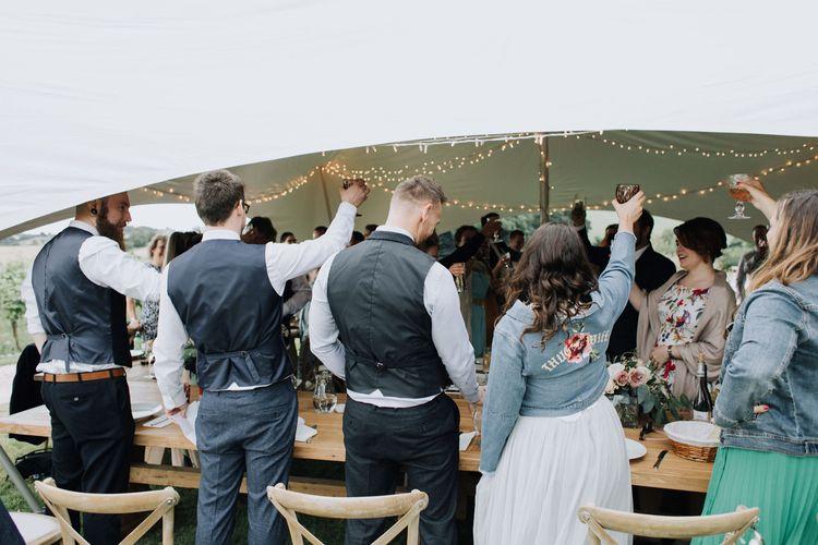 Bride in bespoke denim jacket raising a glass at Brickhouse Vineyard wedding