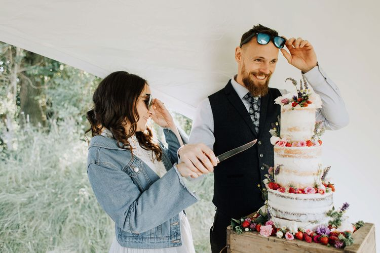 Bride and groom cut the semi naked wedding cake