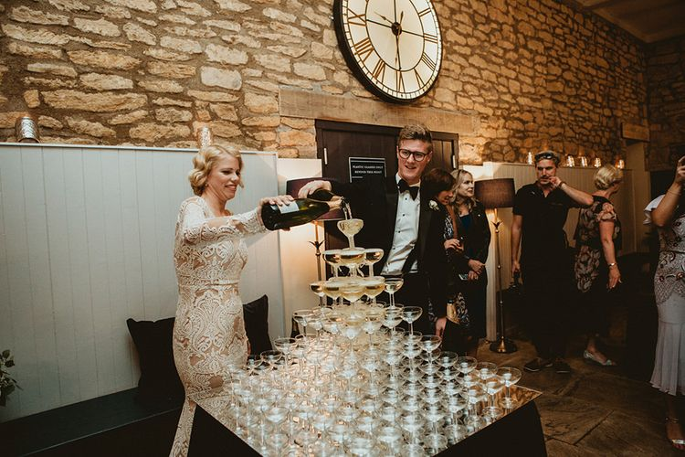 Bride in Vintage Lace Tara Lauren Wedding Dress and Groom in Tuxedo Filling Champagne Tower