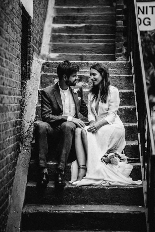 Bride in Reformation Dress   Groom in Blue Richard James Suit   Stylish City Wedding at Bow Arts  Courtyard   Marble Stationery, Wild Flowers & Tissue Tassels Decor   Joanna Bongard Photography