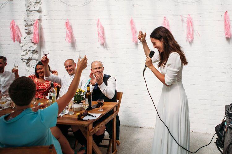 Reception Speeches   Bride in Reformation Dress   Stylish City Wedding at Bow Arts  Courtyard   Marble Stationery, Wild Flowers & Tissue Tassels Decor   Joanna Bongard Photography