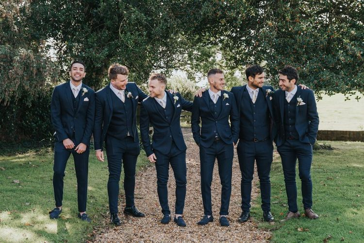 Groom and groomsmen in matching navy suits