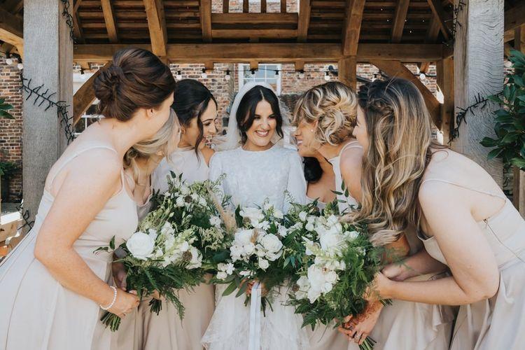 Bridesmaids in neutral bridesmaid dresses