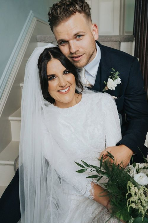 Bride and groom embracing on the stairs
