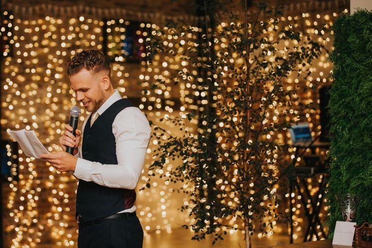 Groom makes wedding speech with fairy light backdrop