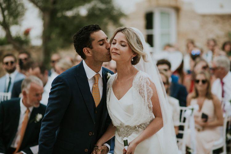 Outdoor Wedding Ceremony with Groom i Navy Blue Suit Greeting his Bride in Halfpenny Wedding Dress