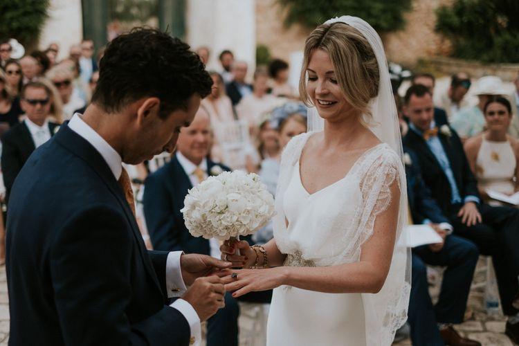 Outdoor Wedding Ceremony with Groom Putting On His Bride in Halfpenny Wedding Dress Wedding Ring