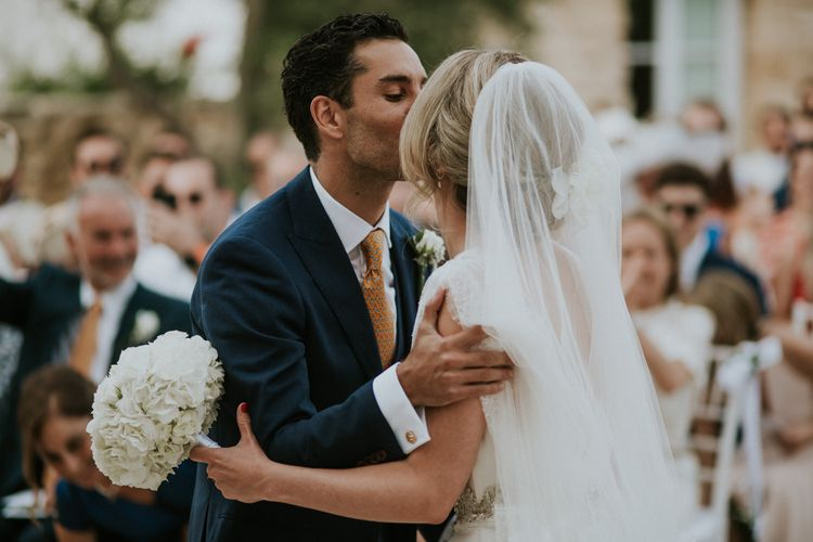 Outdoor Wedding Ceremony  with Bride and Groom Kissing