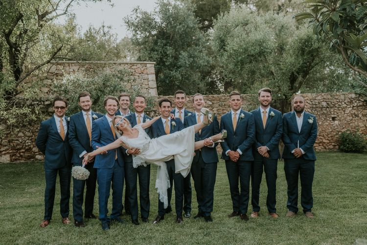 Groomsmen in Navy Blue Suits Holding Up Bride in Halfpenny Wedding Dress