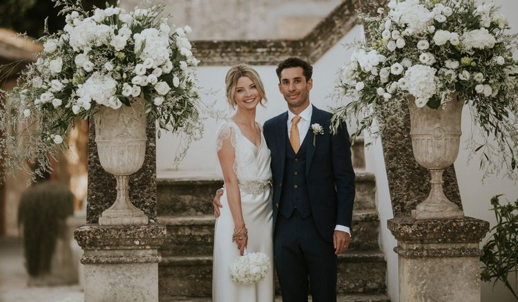 Bride in Halfpenny Wedding Dress and Groom in Navy Suit Posing By  All White Floral Arrangements