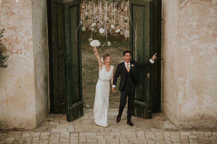 Bride in Halfpenny London Wedding Dress and Groom in Navy Blue Suit Entering the Wedding Breakfast