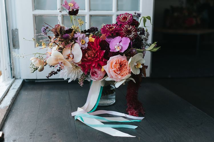 Colourful Deconstructed Bridal Bouquet of Red and Pink Flowers with Trailing Ribbon | Meringue Kisses & Colourful Wedding Flowers & Stationery for a London Wedding at The Globe | Miss Gen