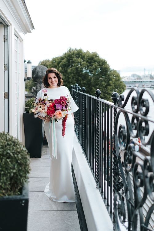 Bride in Halfpenny London Dress with Cowl Back and Half Length Sleeves | Colourful Deconstructed Bridal Bouquet of Red and Pink Flowers with Trailing Ribbon | Tilly Thomas Lux Headband | Meringue Kisses & Colourful Wedding Flowers & Stationery for a London Wedding at The Globe | Miss Gen