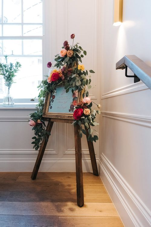 Wedding Welcome Sign in Gold Frame | Wooden Easel | Eucalyptus Garland with Colourful Flowers | Meringue Kisses & Colourful Wedding Flowers & Stationery for a London Wedding at The Globe | Miss Gen