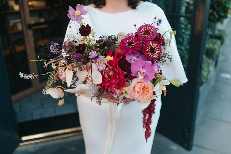 Colourful Deconstructed Bridal Bouquet of Red and Pink Flowers with Trailing Ribbon | Bride in Halfpenny London Dress with Cowl Back and Half Length Sleeves | Meringue Kisses & Colourful Wedding Flowers & Stationery for a London Wedding at The Globe | Miss Gen