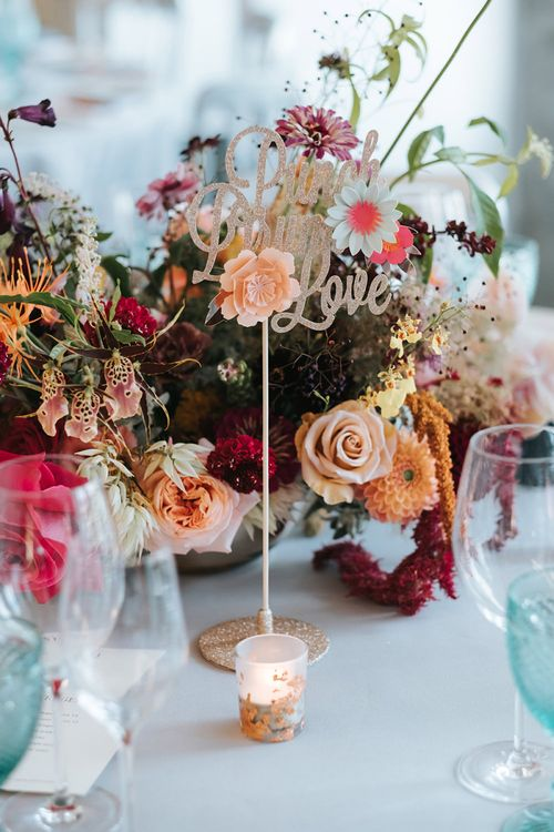 Sparkly Gold Table Sign | Colourful Floral Centrepiece | Tea Light Holder with Gold Glitter Detail | Blue Wine Glasses | Meringue Kisses & Colourful Wedding Flowers & Stationery for a London Wedding at The Globe | Miss Gen