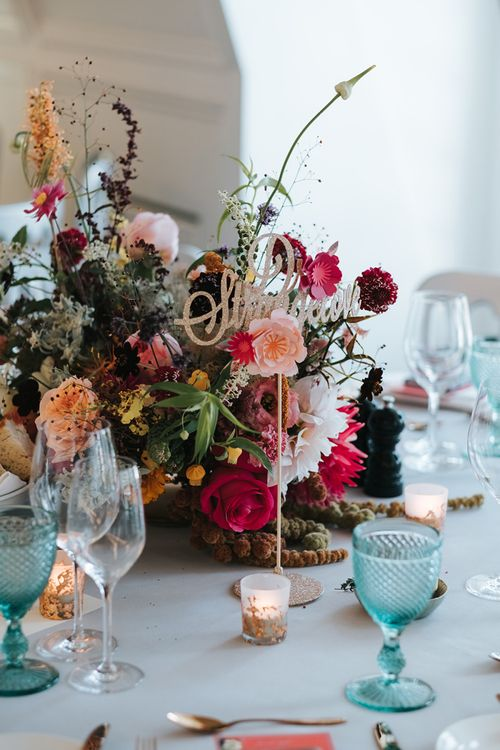 Sparkly Gold Table Sign | Colourful Floral Centrepiece | Tea Light Holders with Gold Glitter Detail | Blue Wine Glasses | Meringue Kisses & Colourful Wedding Flowers & Stationery for a London Wedding at The Globe | Miss Gen