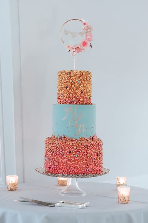 Colourful Three-Tier Wedding Cake with  Duck Egg Blue Icing, Gold Foil Monogram and Pink and Gold Beaded Detail | Copper Hoop Cake Topper with Gold Hearts and Pink Flowers | Tea Light Holders with Gold Glitter Detail | Meringue Kisses & Colourful Wedding Flowers & Stationery for a London Wedding at The Globe | Miss Gen