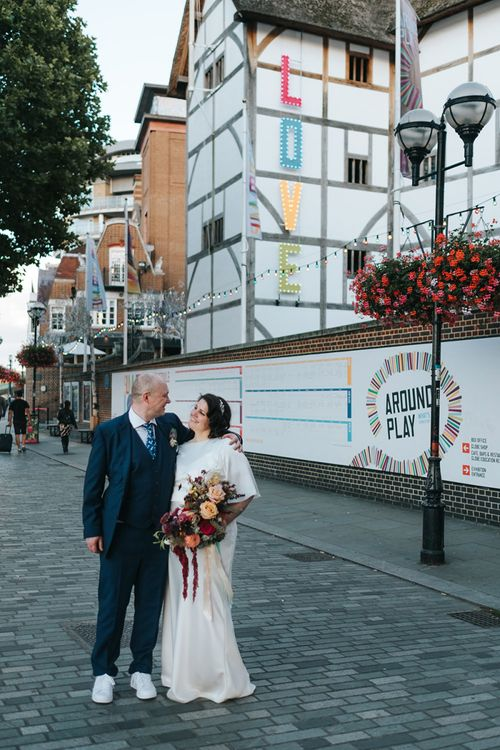 Bride in Halfpenny London Dress with Cowl Back and Half Length Sleeves | Colourful Deconstructed Bridal Bouquet of Red and Pink Flowers with Trailing Ribbon | Tilly Thomas Lux Headband | Groom in Blue Three-Piece Suit and White Trainers | Meringue Kisses & Colourful Wedding Flowers & Stationery for a London Wedding at The Globe | Miss Gen