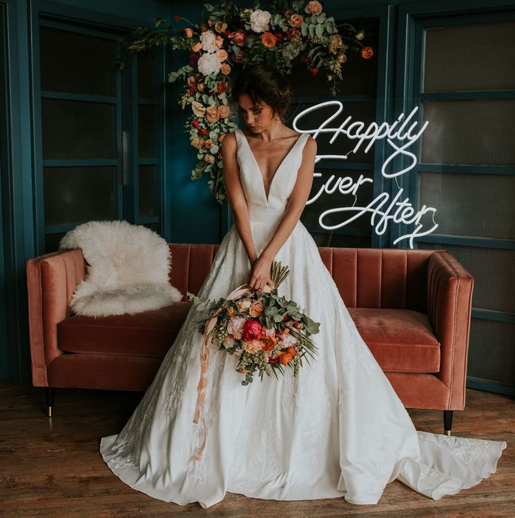 Bride Standing in Front of a Velvet Sofa with Neon 'Happily Ever After ' Sign Backdrop