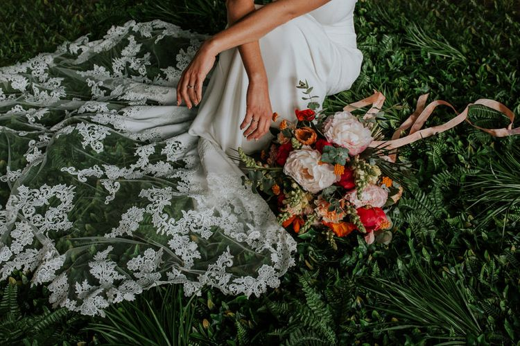 Bride Sitting on Foliage Next to Her Bright Bouquet Showing Off her Lace Wedding Dress Train