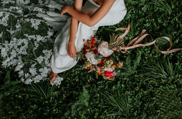 Bride Sitting on The Grass Next to Her Bright Bouquet Showing Off her Lace Wedding Dress Train