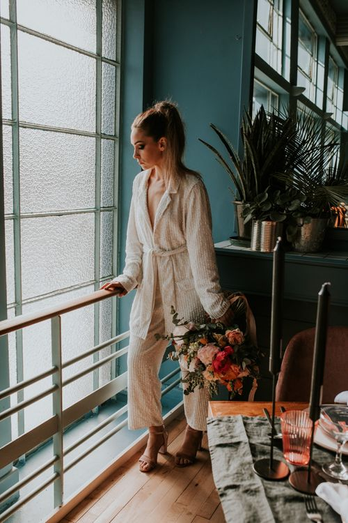Stylish Bride in Wrap Sequin Jump-suit Standing by a Retro Tablescape
