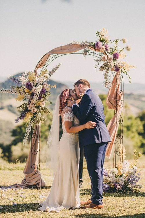 Bride and groom kiss at outdoor ceremony with flower arch