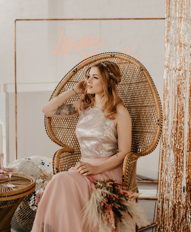 Bridesmaid sitting in a peacock chair in a blush pink and silver dress