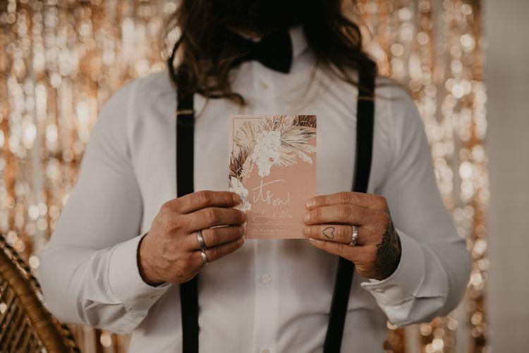 Groom holding a blush pink wedding invitation