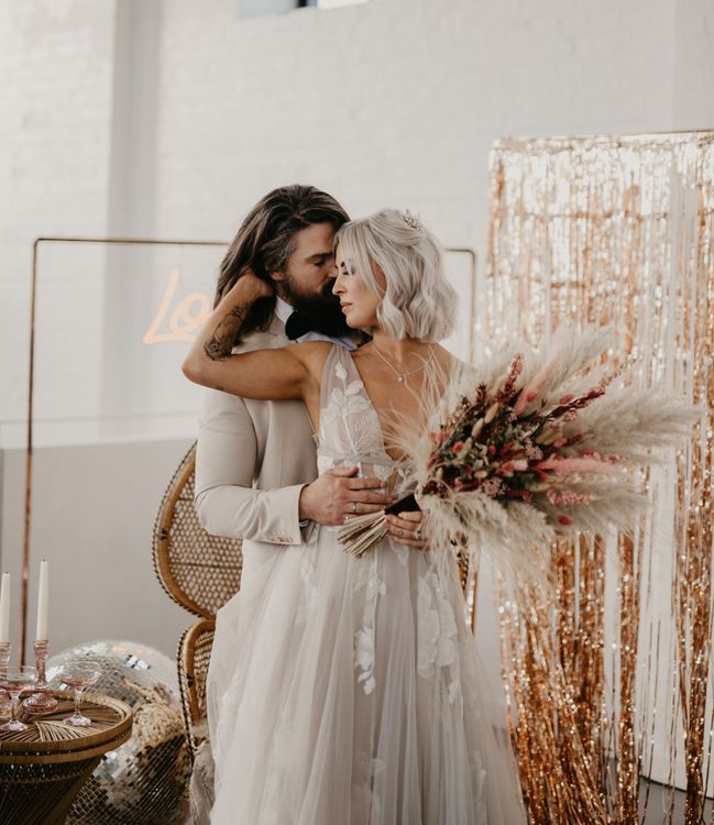 Boho bride and groom wedding portrait with oversized bouquet