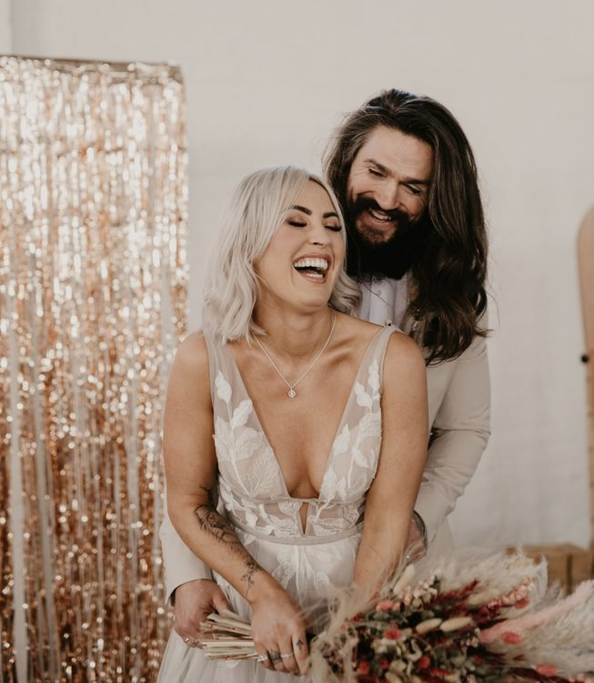 Stylish bride and groom laughing