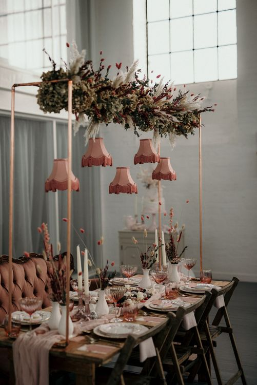 Romantic blush pink wedding reception table decor with hanging flower and lampshade installation