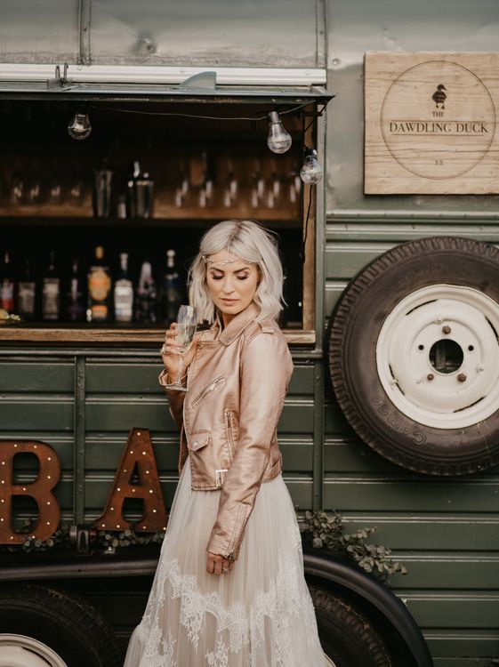Contemporary bride with blush pink leather jacket and platinum blonde hair