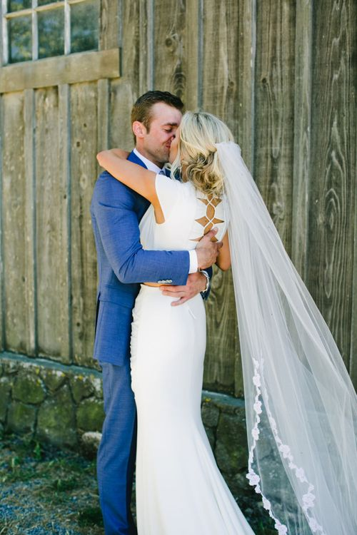 Bride in Noel and Jean Bridal Separates and Wedding Veil Embracing Groom in Blue Suit Supply Wedding Suit