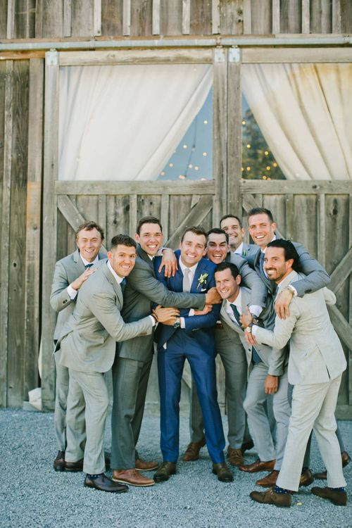 Groom in Blue Suit Surrounded by Groomsmen in Grey Suits