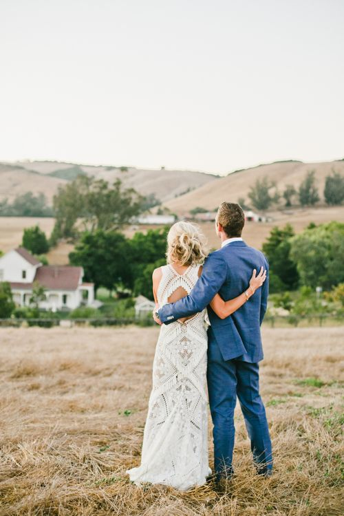 Bride in Lace Rue De Seine Wedding Dress and Groom in Blue Suit  Embracing in the Fields