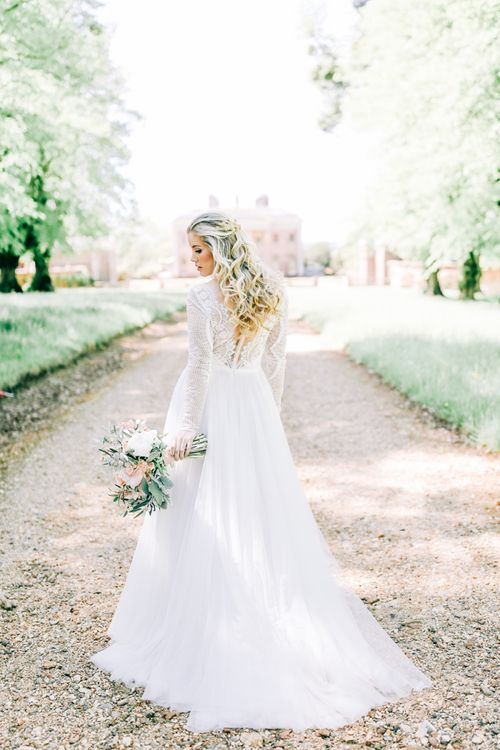 Bride in Lace Wedding Dress Holding White Peony and Peach David Austin Rose Wedding Bouquet and Half up Half Down Wavy Hairstyle