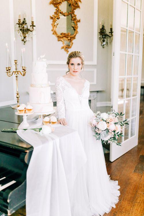Bride in Lace Wedding Dress Standing Next to Elegant Wedding Cake