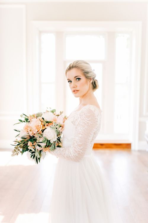 Bride in Lace Long Sleeve Wedding Dress Holding Peach and White Bouquet