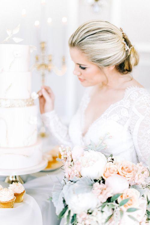 Bride in Lace Long Sleeve Wedding Dress Looking at Elegant Wedding Cake