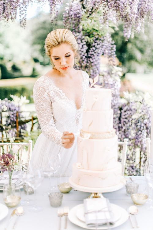 Bride Looking at Marble Effect Wedding Cake with Gold Glitter Layer