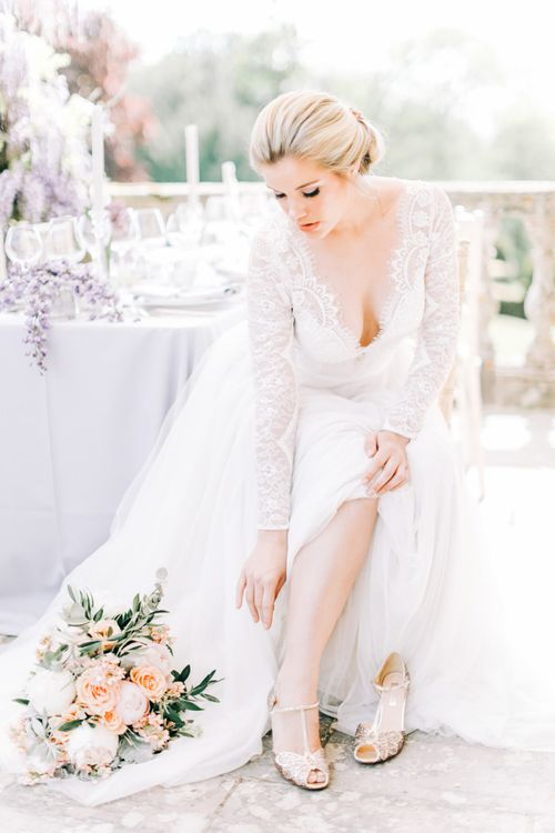 Bride in Lace Wedding Dress putting On Sequin T Bar  Bridal Shoes