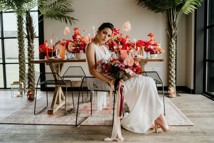 Stylish Bride in Modern Wedding Dress with Pink Bridal Boots holding a Tropical Bridal Bouquet with Anthurium Flower Stems