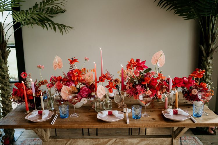 Wedding Table Decor with Red and Pink Floral Centrepiece Flowers with Anthurium Flower Stems, Taper Candles and Coloured Glasses