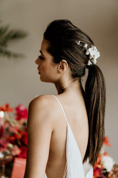 Bride in Minimalist Wedding Dress with Spaghetti Straps and Sleek Ponytail Updo