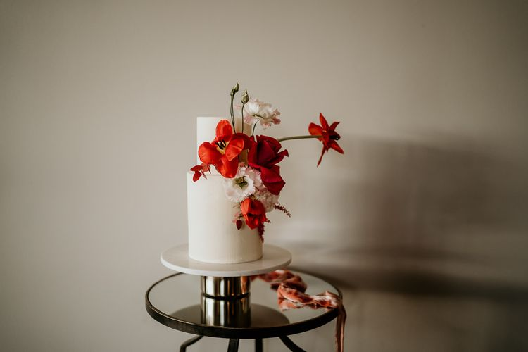 Two Tier Minimalist White Wedding Cake Decorated with Red Wedding Flowers